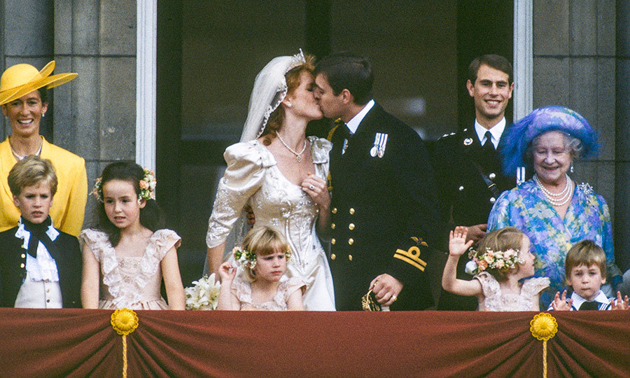 <p>At last! The Duke and Duchess of York shared a sweet kiss on the balcony of Buckingham Palace. Joining the newlyweds on the balcony were Sarah's mother, Susan Barrantes, far left in yellow; best man Prince Edward, right rear; and Queen Elizabeth, the Queen Mother. In the front row, the young wedding attendants included Peter Phillips, far left, and Zara Phillips (now Tindall), centre. </p>
