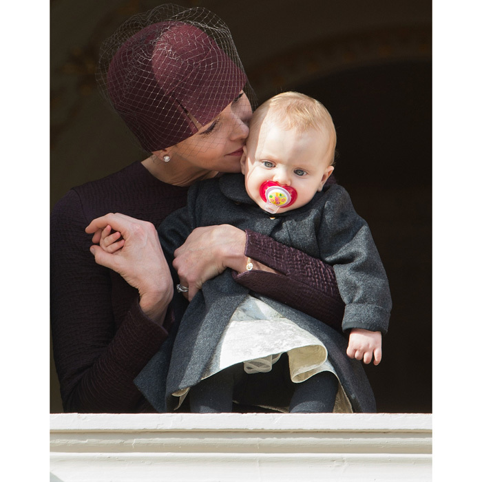 <p>Mommy's little girl! The Monaco royal kissed her daughter while Princess Gabriella observed the crowds below from the palace's balcony during Monaco's 2015 National Day celebrations.</p>