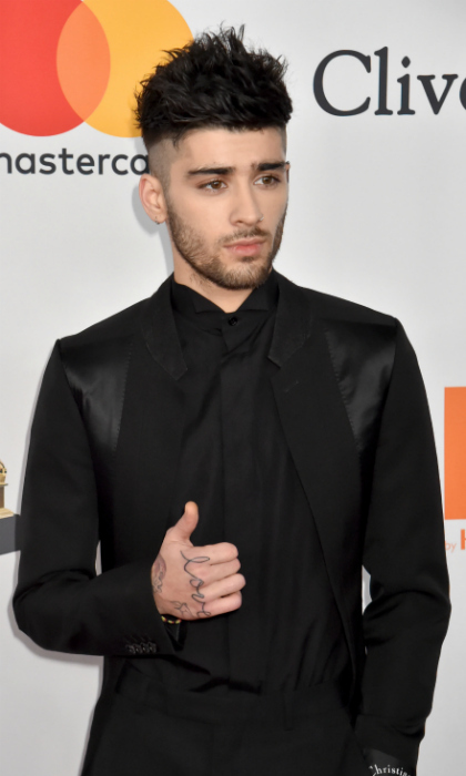 "Thumbs up for the GRAMMYs! Zayn Malik was debonair as he entered the Sheraton New York Times Square event in an all black ensemble. The ""I Don't Wanna Live Forever"" singer opted for a Dior Homme tux.