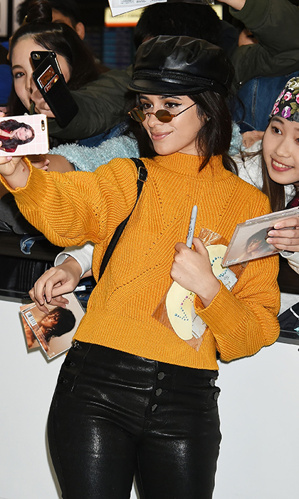 Camila Cabello arrived in Tokyo in style on Jan. 30! The star - wearing a mustard yellow sweater, leather pants and a leather cap - stopped to pose for selfies with adoring fans!