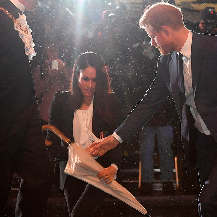 Doting Prince Harry took his beloved bride-to-be's umbrella as they entered Goldsmiths' Hall out of the rain. 