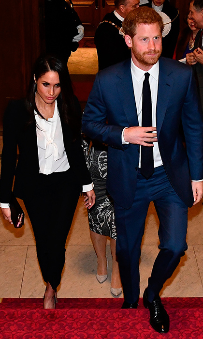 The couple that suits up together stays together! Prince Harry looked dapper in a blue suit, white shirt and skinny black tie paired with shiny black shoes and his manicured scruff. Meghan was a vision in a chic tuxedo look by a favourite brand of her future sister-in-law Kate, Alexander McQueen.