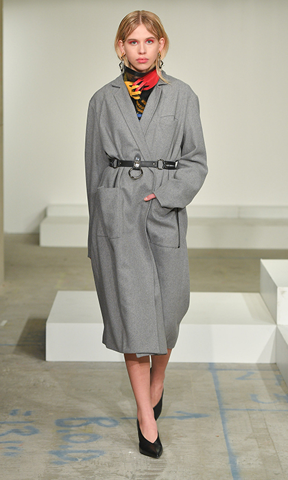"Andrew Coimbra has only been designing since 2015 but his Toronto-based brand has fast become one to watch. Described as ""cool yet refined,"" his aesthetic is right in line with Meghan's personality - and we know this belted grey coat is right up her alley. With a hardware-embellished belt (a collaboration with Uncuffed) and thin lapel, this stunning piece is a twist on the classic and a perfect addition to the bride-to-be's wardrobe for official engagements. 