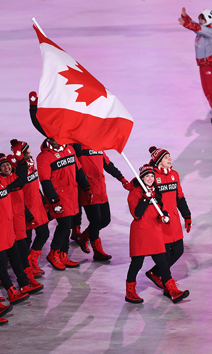 Ice dance partners Tessa Virtue and Scott Moir lead the crowd of Canadian flag bearers.