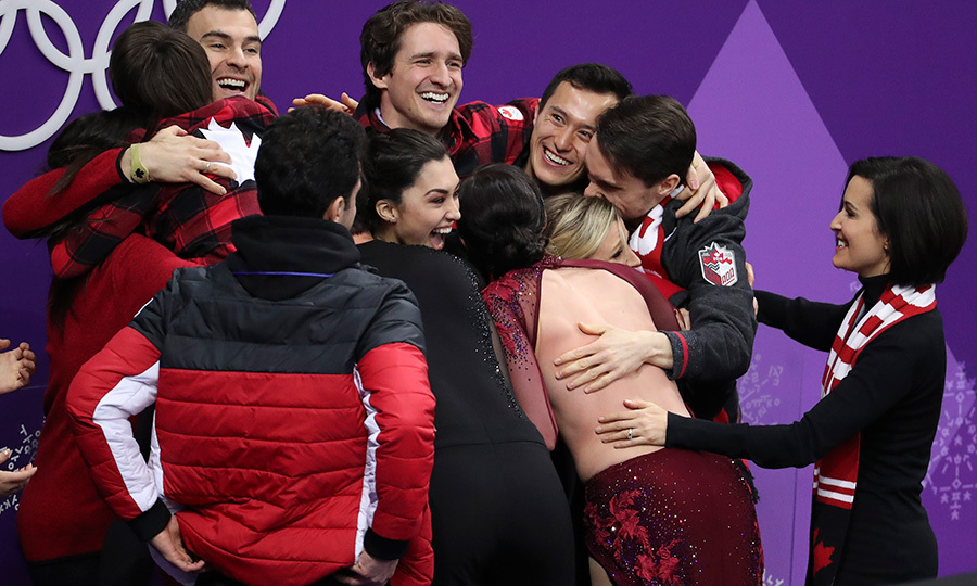 Canadian team members embraced Scott Moir and Tessa Virtue after their stellar performance won them a gold medal.