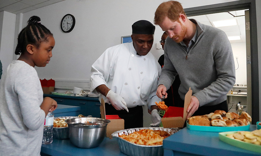The royal served up some delicious-looking lasagna for a kid at the Fit and Fed holiday program.