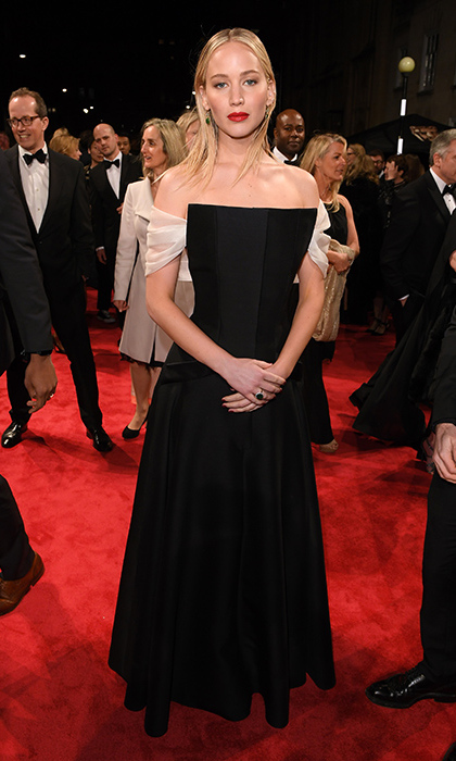 Jennifer Lawrence wore a floor-length satin black dress which featured a unique angular neckline and pretty contrasting white straps which broke up the dress and gave it a modern feel. The 27-year-old added olive gem stone earrings and a splash of red lipstick.