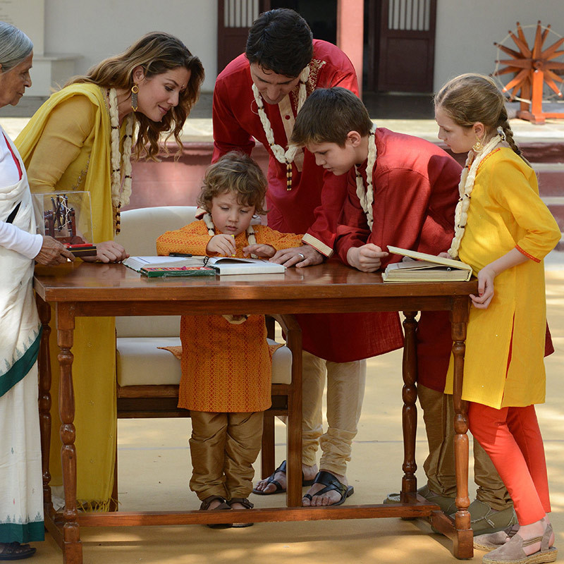 The proud Prime Minister and his wife watched on as their children signed a visitor's book at the ashram. Three-year-old Hadrien took a turn to the delight of onlookers, as did his nine-year-old sister Ella-Grace and brother Xavier, 10. 