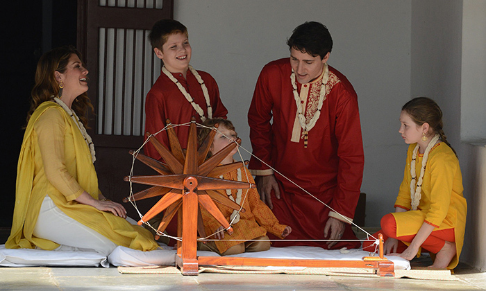 Canada's first family gathered around a ceremonial spinning wheel during their visit to Gandhi Ashram on the second day of their week-long visit to India. 