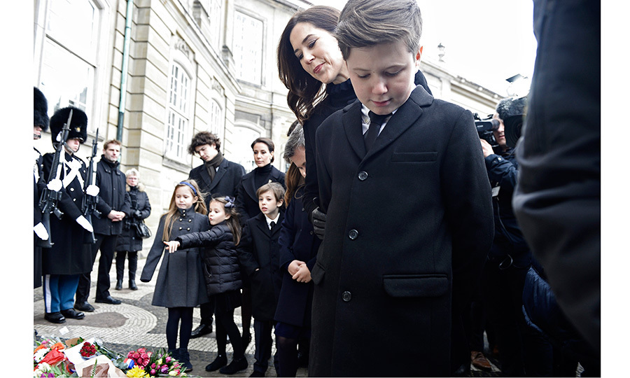 <p>Also there to help guide the young Princes and Princess as they publicly mourned their grandfather was Henrik's daughter in law, Crown Princess Mary, wife of Crown Prince Frederik. Here, with Princess Marie and Henrik's grandchildren seen in the background, Mary and Prince Christian look at the floral arrangements left by well-wishers.</p>