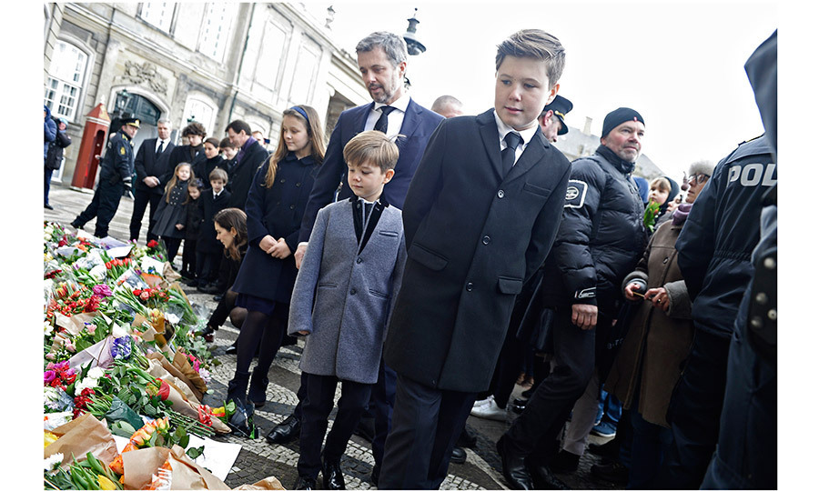 <p>Here Crown Prince Frederik is seen with his 12-year-old son, second-in-line Prince Christian, seven-year-old son Prince Vincent, and ten-year-old daughter Princess Isabella, as they look at flowers left by mourners in front of Amalienborg Palace on February 15. Behind them are Crown Princess Mary, kneeling, as well as Henrik's younger son Prince Joachim with his children and wife Princess Marie.</p>
