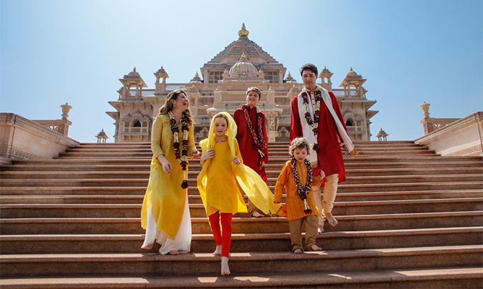 Clad in complementary shades of yellow, red and orange, the Trudeau family posed for a striking snap on the stairs outside the temple.