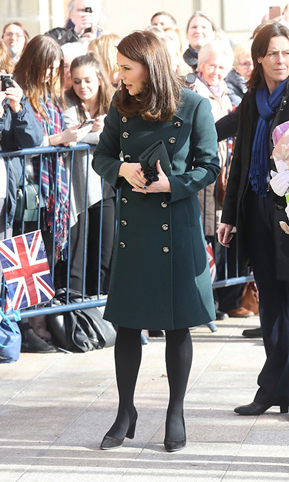Wearing a beautiful military coat in a deep green hue by Dolce & Gabbana, pregnant Kate stunned crowds in Sunderland on a day out with Prince William Feb. 21. She anchored her look with black tights and suede pumps, carrying a simple black clutch and accenting the look with delicate jewelry. Fresh makeup and her signature blow dry highlighted her natural beauty. 