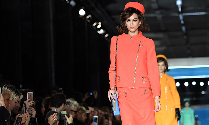 Cindy Crawford's supermodel daughter Kaia Gerber was giving off major Jackie O vibes on the runway at Moschino during Milan Fashion Week. Jeremy Scott's collection was inspired by the jet-setting women of the 1960's as they saw the future - hence the sherbet-hued skirt suits with pillbox hats bedecked with space-age zippers. 