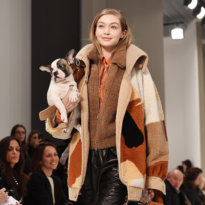 <p>The only thing sweeter than the natural makeup at the Tod's show was the parade of pups that took to the runway. Here's Gigi Hadid toting an adorable little pal on the 'dogwalk' on February 23.</p>
