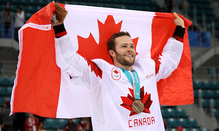 Men's hockey defenceman Cody Goloubef, #27, skated with the Canadian flag after Team Canada beat the Czech Republic 6-4 to take home the bronze medal. 