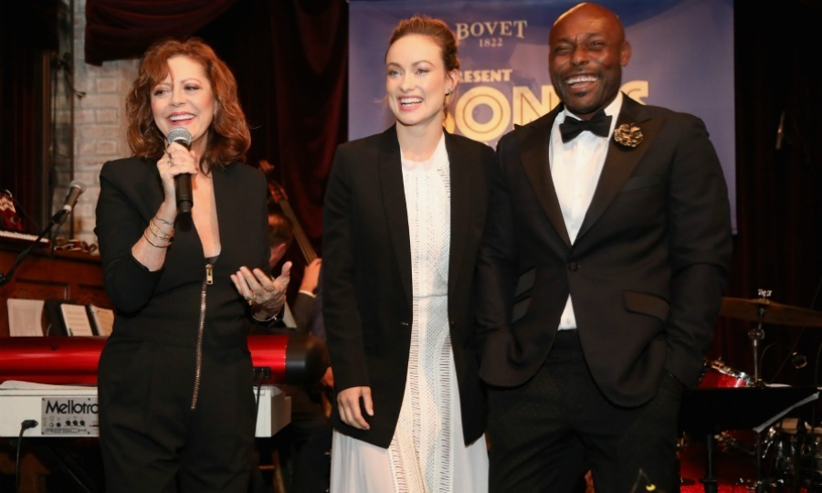 "Susan Sarandon spoke onstage with Olivia Wilde and event co-host Jimmy-Jean Louis at BOVET 1822 & Artists for Peace and Justice present ""Songs from the Cinema Benefit"" on March 3 in L.A. The stars both serve as Board members for the foundation. The evening celebrated Oscars week while raising much-needed funds to support the tireless efforts of APJ, which brings education and training in creative industries to the youth of Haiti, while encouraging peace and social justice and addressing issues of poverty around the world.