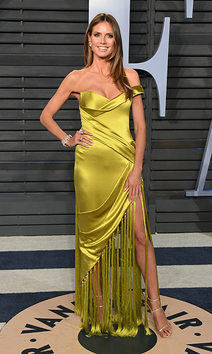 <p>Heidi Klum hit the party circuit in a yellow satin off-the-shoulder gown with fringe details, paired with strappy heels.</p>