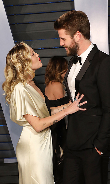 Was red carpet veteran Miley Cyrus giving her beau Liam Hemsworth some posing tips?