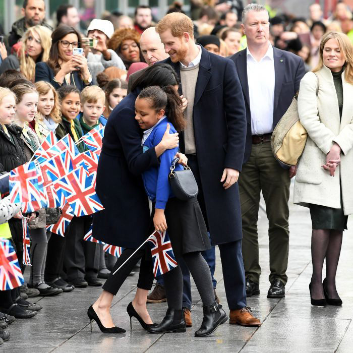 <p>The 36-year-old broke royal protocol by giving the schoolgirl a big hug after they first formally shook hands. Prince Harry stood close by, and smiled at the other children who lined their entrance to Millennium Point.</p>