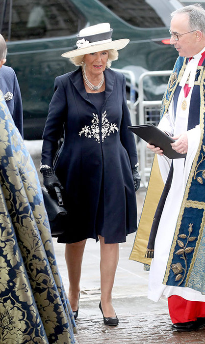 Camilla, Duchess of Cornwall, arrives at Westminster Abbey in a gorgeous blue and white coat. The royal accessorized with a beautiful hat and leather gloves.