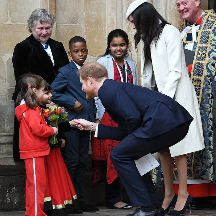 Prince Harry took a turn to crouch down and shake hands with two adorable fans.