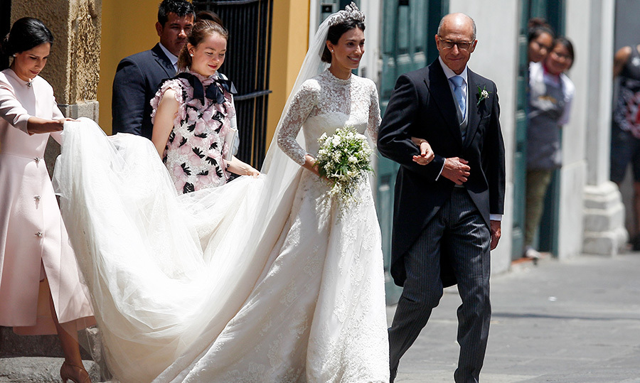<p>How stunning does Alessandra look? The bride wore a high-necked, long-sleeved wedding gown by Jorge Vazquez with the most beautiful train. Her tiara perched perfectly atop her dark hair as her father walked her towards the Basilica.</p>