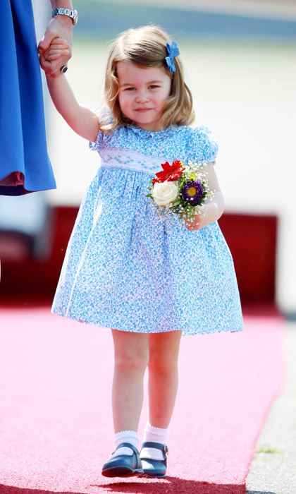 <a href=/tags/0/princess-charlotte><strong>Princess Charlotte</strong></a> carried her first posy as she walked hand-in-hand with her mother upon their arrival at Berlin Airport. The tiny princess wore a darling blue floral print dress and finished her look with a matching bow and Mary Jane shoes.