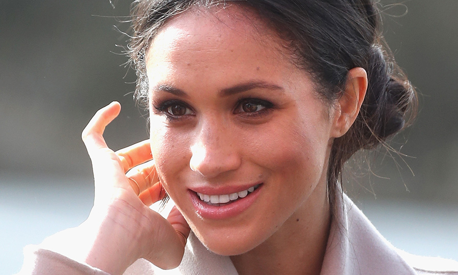 Meghan wore her glossy brown locks, which she has coloured by Toronto's Luis Pacheco at Medulla & Co., in a chic side bun. In an uncharacteristic turn, the style icon - who usually makes a statement with her earrings - left her lobes bare.