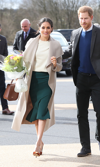 <p>Meghan pulled out all the stops for her and Prince Harry's royal engagement in Belfast, Ireland. The former actress was the picture of elegance in rust velvet Jimmy Choo pumps, emerald green skirt, blush coat by Canadian designer Package, a white knit by Victoria Beckham and a chic brown handbag by Charlotte Elizabeth.</p>