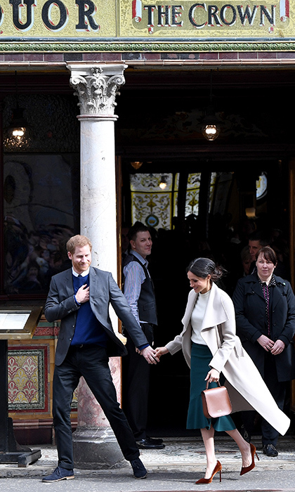 After a visit to The Crown Liquor Saloon, of of Ireland's best-known pubs that dates back to the 19th century, Meghan held onto Harry's hand as they headed to the next spot on their whistle-stop tour.