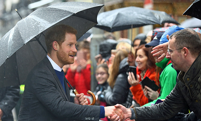 Prince Harry also had an umbrella on hand to greet fans in the rain!
