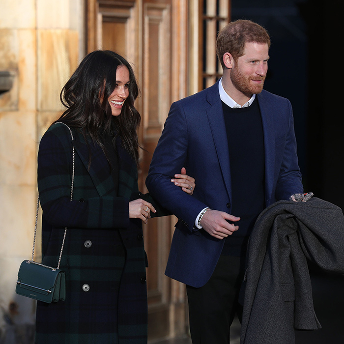 <p>Meghan held on the Harry's arm as the two made an official appearance.</p>