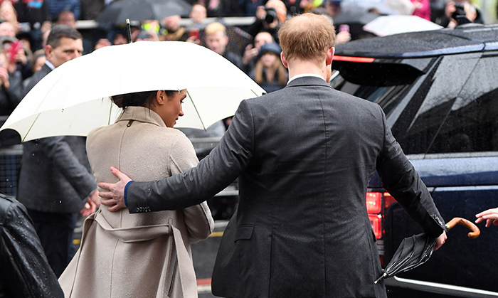 <p>With a hand on his bride-to-be's back, Prince Harry directed Meghan to shelter from the rain.</p>