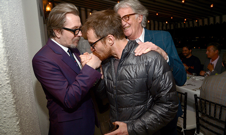 <p>Oscar winner Sam Rockwell planted a friendly smooch on Gary Oldman's hand while Paul Smith looked on at their dinner party on April 10.</p>