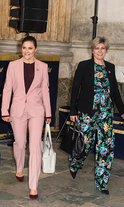 <p>Is Meghan Markle's penchant for pantsuits rubbing off on Crown Princess Victoria? Here, the royal stunned in a blush pink and maroon ensemble while attending the Global Child Forum on Apr. 11.</p>