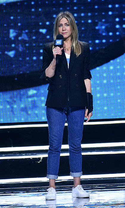 <p>Jennifer Aniston sported a wrist brace on the WE Day stage on April 19. The star, who recently separated from ex-husband Justin Theroux, looked cool and casual in a pair of white sneakers, blue jeans and a tailored blazer.