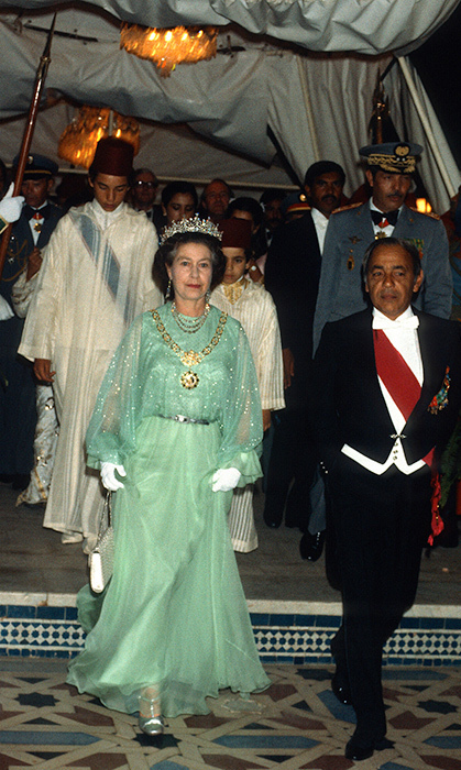 <p>While attending a banquet in Morocco in 1980, the Queen debuted this amazing teal gown and even a tiara! But what we're loving most are her matching metallic shoes.