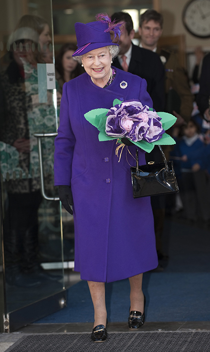 <p>The Queen has just as many jewel tones in her wardrobe as she has jewels in her jewelry box! She clutched a bouquet while visiting a primary school in London in 2010.