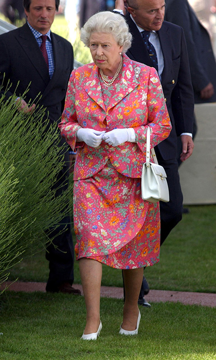 <p>Always willing to wear a pop of colour, the Queen matched her lipstick to her dress while attending a Queen's Cup polo match 2004.