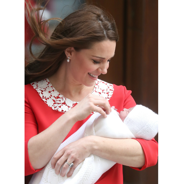 Kate takes a moment to admire her newborn son on the steps of the Lindo Wing. The mother-of-three dazzled in a crimson red dress by Jenny Packham. Baby Cambridge looked adorable swaddled in a white blanket and matching bonnet. 