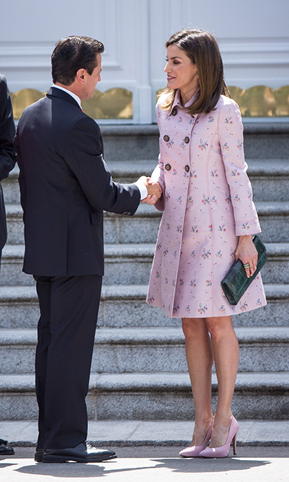 <p>Queen Letizia was the picture of spring in pink suede pumps and a pink floral a-line coat. She accessorized with a chic grey velvet clutch, keeping her hair straight and natural.</p>