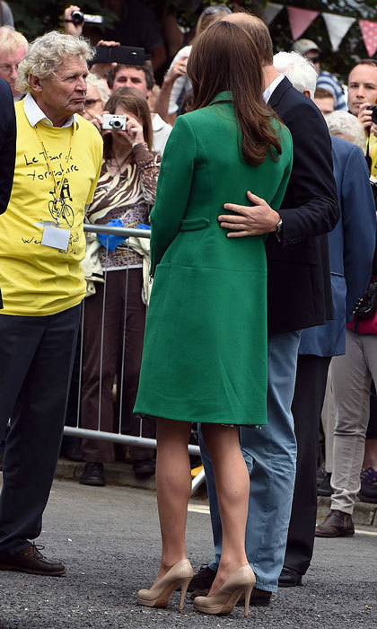 William's got Kate's back! The Duke of Cambridge sweetly held his wife during a 2014 visit to a Yorkshire village celebrating the Stage 1 route of the Tour de France.