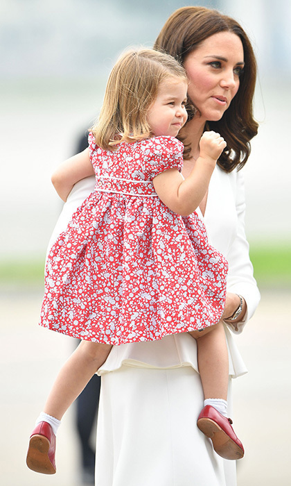 During the little Cambridge's second tour to date, this time in Poland, Charlotte touched down in Warsaw with her parents and brother George wearing a sweet red Liberty-print dress, white socks and a very special pair of shoes. The family heirlooms, burgundy Mary Janes, were originally worn by her uncle Prince Harry in 1986 when the almost-to-year-old posed for portraits with his family. 