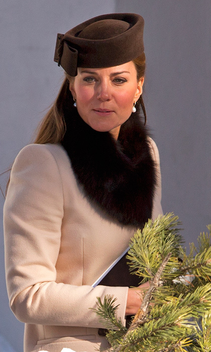 We got to see a rare cold-weather wedding look from the Duchess of Cambridge at the March 2013 nuptials of Laura Bechtolsheimer and Mark Tomlinson in Arosa, Switzerland. Then pregnant with son Prince George, Kate wore a simple beige coat with a faux fur scarf and pillbox hat. 
