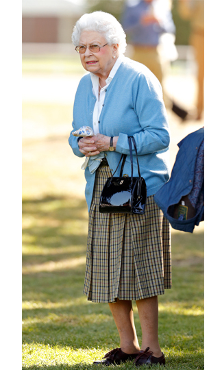 <p>Queen Elizabeth was her typical stylish self – decked out in a pale blue cardigan and plaid skirt – while at the horseback riding event.</p>