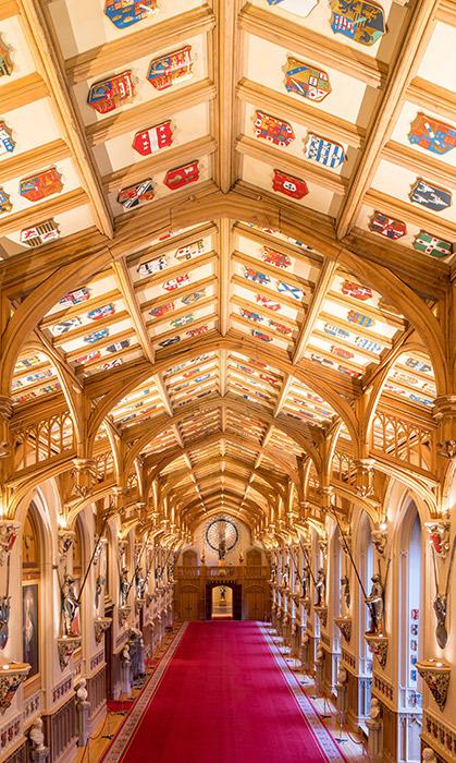 <p>The gothic design was envisioned and created by <strong>Giles Downes</strong>, who decorated the ceiling with colourful shields celebrating the Order of the Garter. This hall is actually the longest room in Windsor Castle, measuring in at a whopping 180 feet!</p>