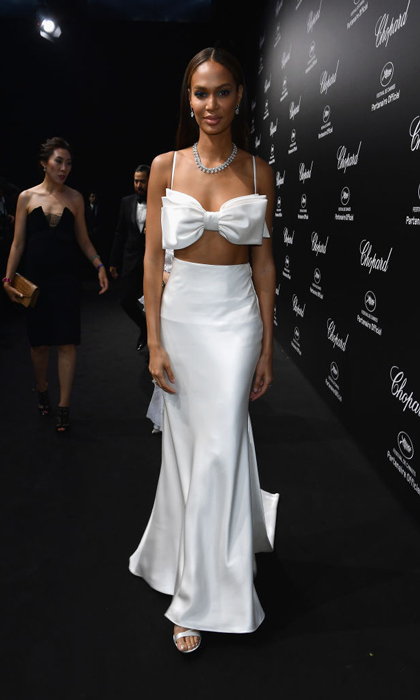 <p>Two outfits are better than one! Joan Smalls wore a unique two-piece white ensemble for the Chopard party, then changed into a royal blue mini dress for a party with Grey Goose.</p>