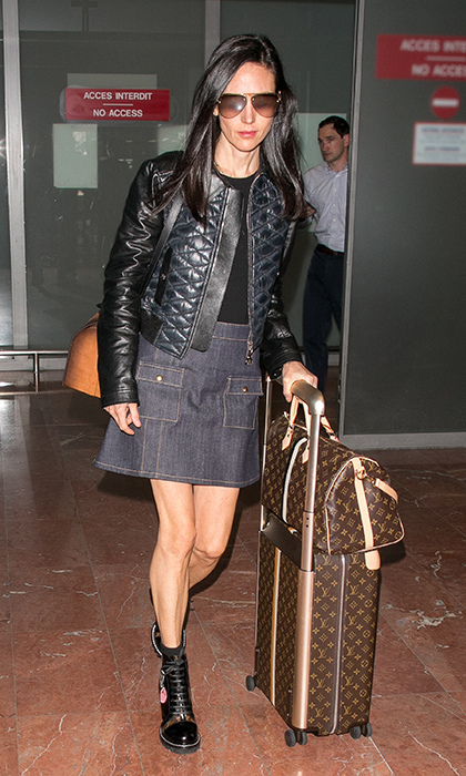 Jennifer Connelly's airport look was totally on point at she toted multiple Louis Vuitton bags wearing black combat boots, an A-line denim skirt, a black t and quilted leather jacket. 