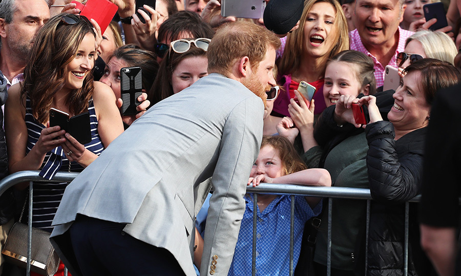 <p>Harry leaned over to chat with some little ones waiting to meet him. They were clearly overjoyed to get some face time with the prince!</p>